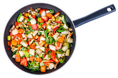Skivade grönsaker i den isolerade pannan Arkivfoto