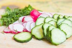Skivade grönsaker på brädet Arkivbilder