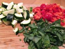 Skivade grönsaker på en skärbräda landskap tätt upp Royaltyfri Foto