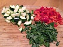 Skivade grönsaker på ett skärbrädalandskap Arkivbild