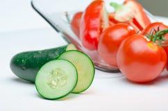 Skivade grönsaker på vitbakgrund för Glass platta Arkivbilder