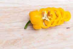 Skivade gula nya spanska peppar på träskärbräda royaltyfri fotografi