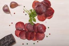 Skivade hästkorv, örter och kryddor på skärbräda Arkivfoto