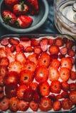 Skivade jordgubbar för kaka på det lantliga köksbordet, bästa sikt royaltyfri fotografi