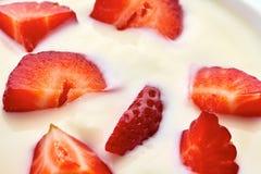 Skivade jordgubbar i yoghurt arkivfoton