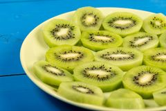 Skivade Kiwi Fruit On The Plate med bl? tabellbakgrund royaltyfri foto