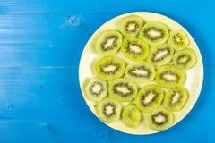 Skivade Kiwi Fruit On The Plate med bl? tabellbakgrund arkivfoto