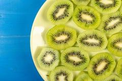 Skivade Kiwi Fruit On The Plate med bl? tabellbakgrund royaltyfri bild