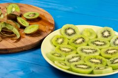 Skivade Kiwi Fruit On The Plate och träskärbräda royaltyfria foton
