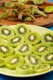 Skivade Kiwi Fruit On The Plate och tr?sk?rbr?da arkivfoton
