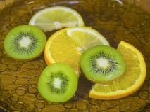 Skivade Kiwi Lemon Orange i vatten Royaltyfria Foton