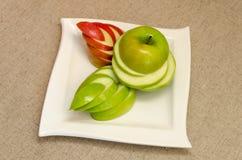 Skivade läckra äpplen på en vit platta Arkivbild