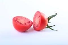 Skivade nya tomater med gröna sidor på vit bakgrund Royaltyfri Fotografi