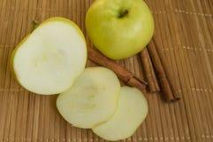 Skivade och hela gröna Apple med kanelbruna pinnar på bambuservett Royaltyfri Foto