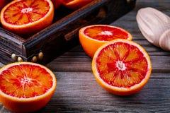 Skivade och hela mogna saftiga Sicilian blodapelsiner på träbakgrund Arkivfoto