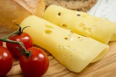 Skivade ost och körsbärsröda tomater på träskärbräda Royaltyfri Bild
