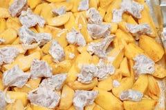 Skivade potatisar med kött som är rått på en bakplåt Fotografering för Bildbyråer
