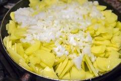 Skivade potatisar med lökar i en stekpanna Arkivfoto