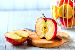 Skivade röda Apple på det wood brädet Arkivbild