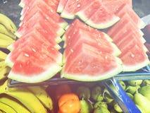 Skivade skivor av vattenmelon ligger bredvid olika frukter Vattenmelon i ett snitt Royaltyfria Foton