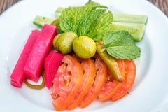 Skivade tomater, gurkor, oliv och grönsaker på en platta Arkivbild
