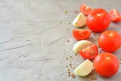 Skivade tomater och lökar på en grå bakgrund Arkivfoto