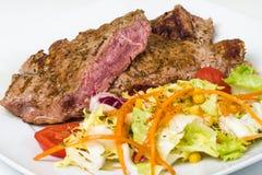 Skivakalvkött som är sällsynt med sallad på plattan Arkivbild
