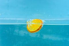 Skivan av apelsinen under vatten med genomskinliga bubblor och vatten tappar färgstänk Coctaildanandebegrepp Apelsin i rent Arkivfoto