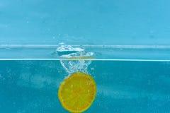 Skivan av apelsinen under vatten med genomskinliga bubblor och vatten tappar färgstänk Fruktnedgång in i vatten, blå bakgrund Royaltyfria Bilder