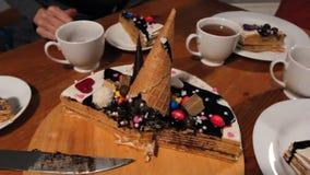Skivan av blommor för choklad och för kräm för chokladpralinnisse kakan överträffade vita med varmt te rånar dekorerat med frukte stock video