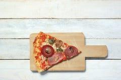Skivan av hemlagad pizza 4 kryddar i en vit trätabell Royaltyfri Foto