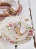 Skivan av kaka`-Ciambellone ` med smulor på den keramiska plattan målade med blom- motiv royaltyfri foto