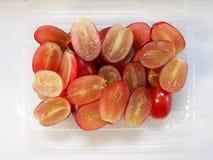 Skivan av röda druvor i den plast- asken som är klar för, äter för bantar Arkivbild