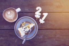 Skivan av stearinljuset för witn för födelsedagkakan numrerar en och två med koppen av latte på trätabellen i varmt solljus royaltyfri foto