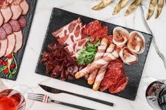 Skivar kallt kött för Antipastouppläggningsfatet med grissinibrödpinnar, prosciutto, skinka, knyckigt för nötkött, salami kritise arkivfoto