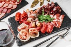 Skivar kallt kött för Antipastouppläggningsfatet med grissinibrödpinnar, prosciutto, skinka, knyckigt för nötkött, salami kritise royaltyfri fotografi