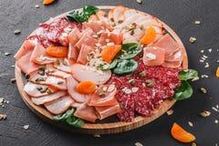 Skivar kallt kött för Antipastouppläggningsfatet, prosciutto, skinka, knyckigt för nötkött, salami, kött och muttrar på skärbräda royaltyfria foton