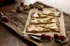 Skivar pizza med champinjoner med brun bakgrund arkivbilder