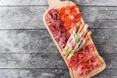 Skivar plattan för kallt kött för Antipastouppläggningsfatet med grissinibrödpinnar, prosciutto, skinka, knyckigt för nötkött, sa arkivfoton