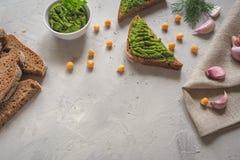 Skivat bröd för helt vete med guacamole, kikärten och vitlök på den gråa konkreta bakgrunden royaltyfri bild