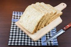 Skivat bröd för helt vete på att hugga av trä- och borddukbackgro Royaltyfria Foton