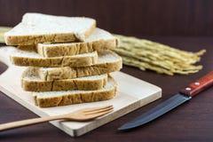 Skivat bröd för helt vete på att hugga av trä och handen stack backg Arkivfoton