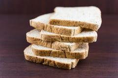 Skivat bröd för helt vete på den wood tabellen Royaltyfri Bild