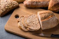 Skivat bröd på den gråa stentabellen, kniv, slut upp arkivfoto