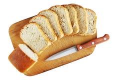 Skivat bröd på en skärbräda Arkivbild
