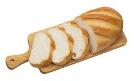 Skivat bröd på träskärbrädan som isoleras på vit bakgrund arkivbilder
