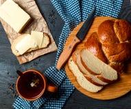 Skivat bröd, smör och te på en mörk bakgrund Top beskådar Arkivfoton
