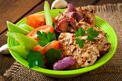 Skivat griskött som grillas med grönsaker Arkivfoton