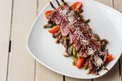 Skivat medelsällsynt steknötkött med knipor, körsbärsröda tomater, champinjoner på en vit platta på träbakgrund royaltyfri fotografi