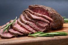 Skivat nötkött för stek för gräsFed saftigt havre som garneras med Rosemary Fresh Herb på naturlig träskärbräda royaltyfria foton